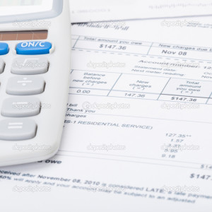 Utility bill and calculator over it - 1 to 1 ratio